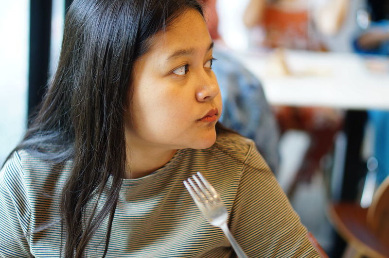 Close-Up Of Woman Looking Away At Restaurant