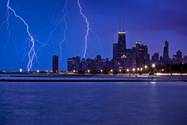 Idyllic view of lightning over illuminated city and river at dusk