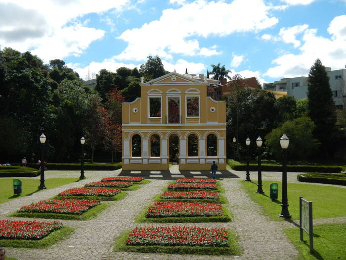 View of building in garden against cloudy sky