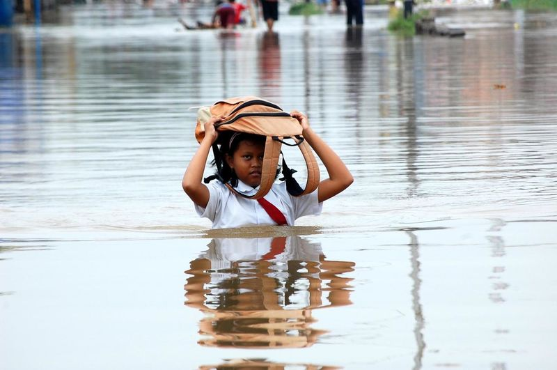 Portrait of girl with bag on head walking in water