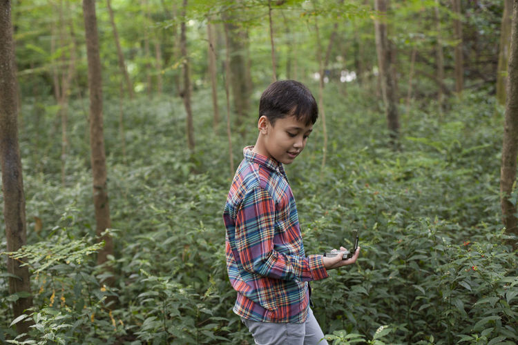 Young Boy with Compass 9-11 Adventure Asian Boy Boy Compass Direction Eco Tourism Forest Guidance INDONESIA Indonesian Nature Navigational Compass One Person Outdoors People Standing Tree Young Young Adult