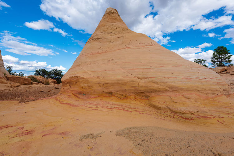 Low angle landscape of large yellow striped conical rock formation at ojito wilderness in new mexico