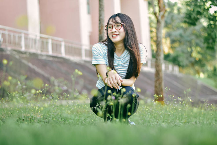 Cheerful young woman crouching on grass against building at park