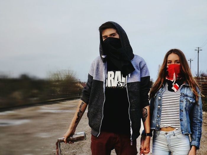 Portrait of young couple hiding face with bandana while standing on field