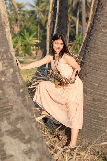 Portrait of beautiful smiling woman standing in the middle of a tree with a saxophone