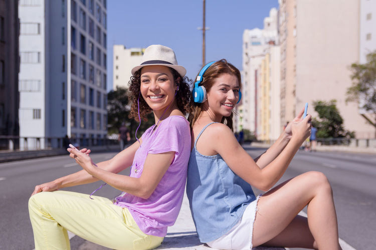 Headphones Music Architecture City Emotion Hairstyle Happiness Leisure Activity Lifestyles Looking At Camera Outdoors Portrait Real People Sitting Smiling Technology Three Quarter Length Togetherness Two People Wireless Technology Women Young Adult Young Women