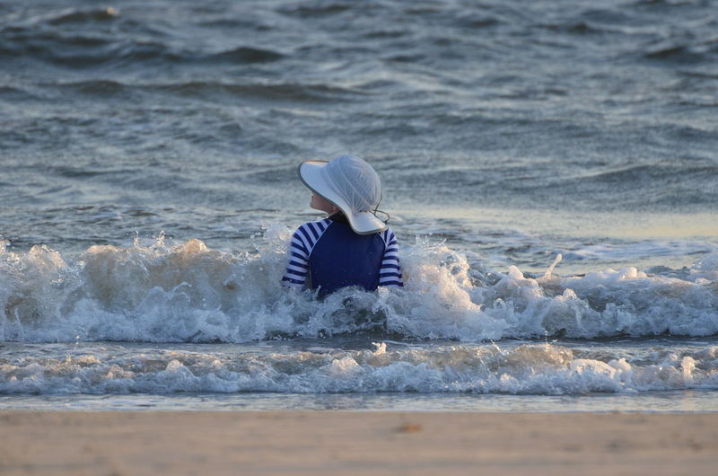 Beach Hat Beauty In Nature Blue Child On Beach Day Focus On Foreground Leisure Activity Lifestyles Nature One Child Outdoors Playing In The Water Rippled Selective Focus Sitting In The Surf Splashing Waves Tranquil Scene Tranquility Vacations Water Waves