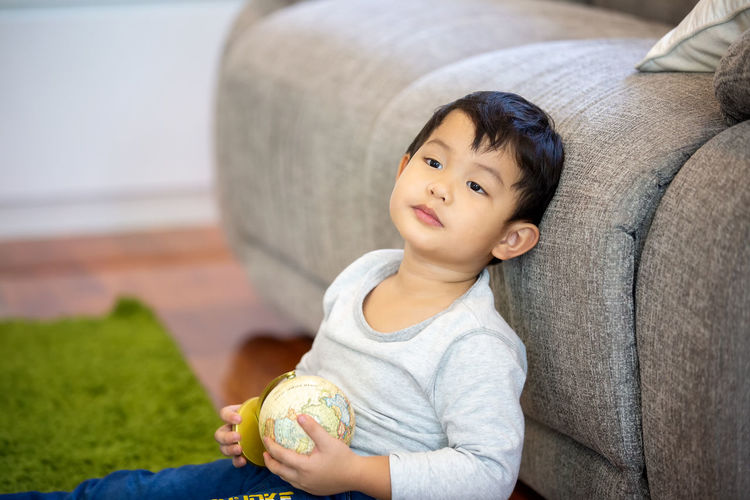 Cute boy sitting with globe against sofa at home