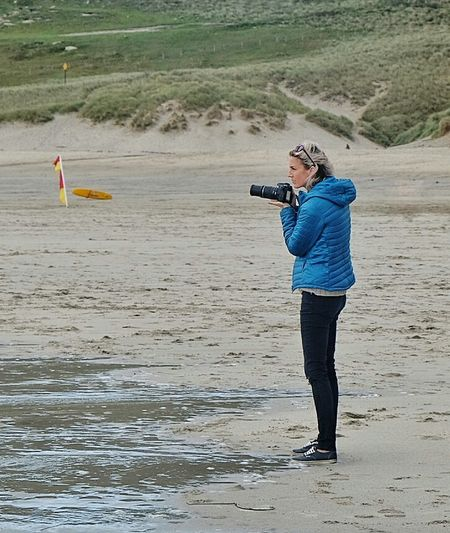 Full length of man photographing on beach