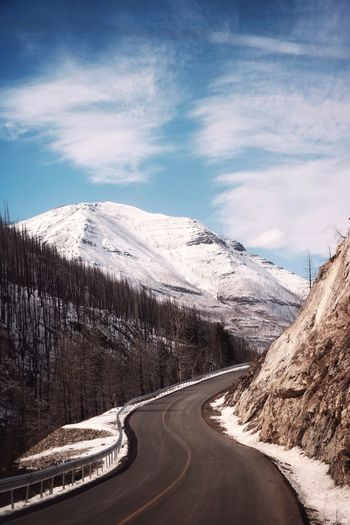 Snow covered road by mountain against sky
