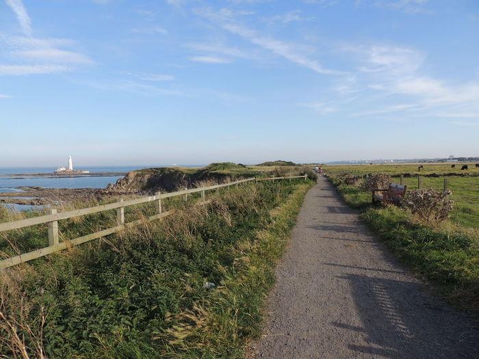 Road leading towards sea against sky