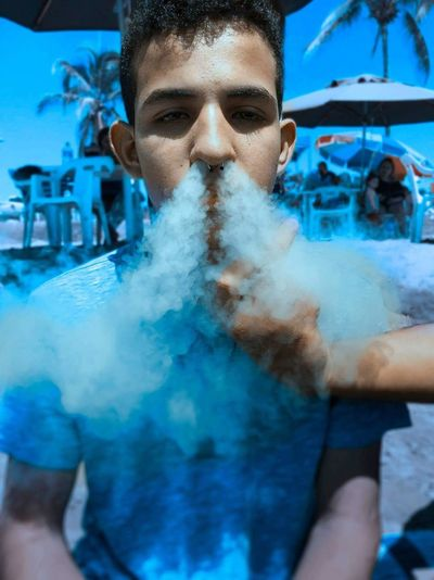 Portrait of young man emitting blue smoke from nose