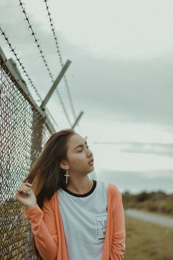 Young woman looking away while standing by fence against cloudy sky