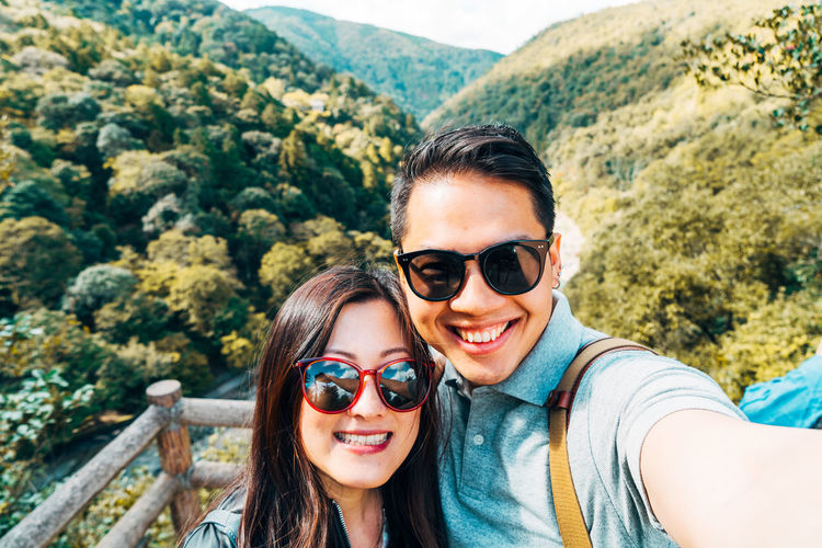 High Angle Portrait Of Smiling Friends Wearing Sunglasses Against Mountains