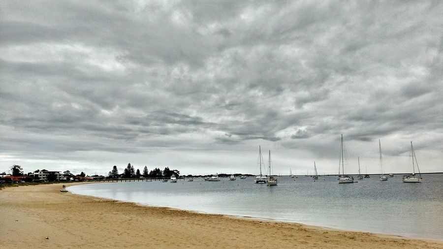 A golden beach around a crescent bay filled with sailboats under stormy skies. Stormy Weather Melancholic Landscapes Forlorn Beach Boats Boats And Moorings Sailboats
