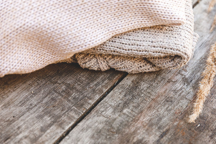 Autumn, winter background. stack of cozy knitted wool clothes sweaters, dried plant on wooden table