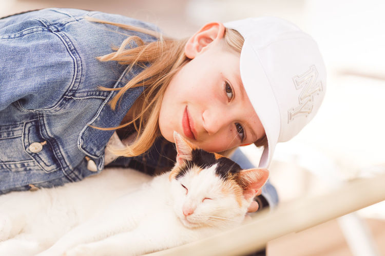 Portrait of girl with cat at home