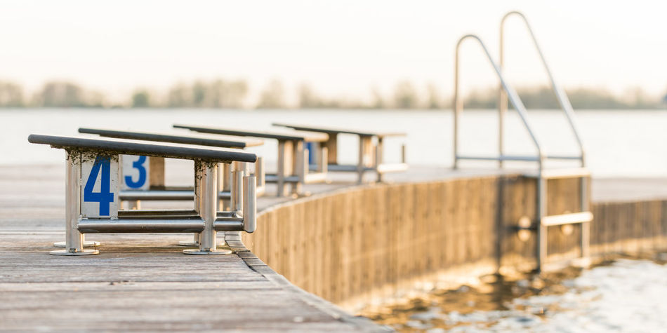 Jetty with starting blocks for swimmers. 4 Morning Light Stairs Swimming The Netherlands Absence Beach Dawn Of A New Day Day Focus On Foreground Jetty Nature No People Outdoor Swimming Pool Outdoors Sea Seat Sky Starting Blocks Swim Swimmingpool Water