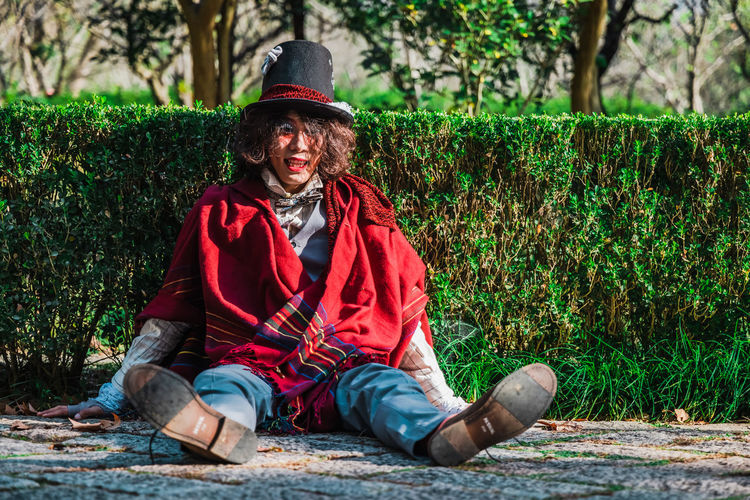 Portrait of smiling man cosplaying mad hatter sitting outdoors next to hedges