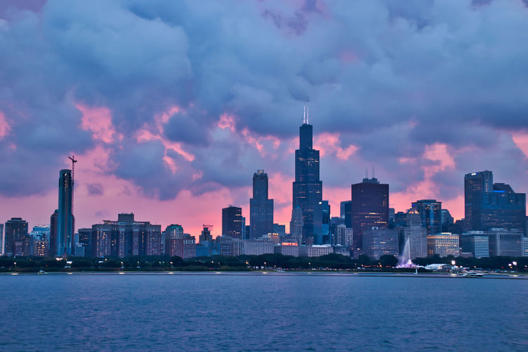 Cloud-covered sunset over city of Chicago skyline during evening, seen from Lake Michigan in summer boat ride. Chicago Chicago Loop Construction Site Downtown Chicago Fountain Lake Michigan Lake Michigan Chicago Marina Skyline Architecture Building Building Exterior Built Structure City Cityscape Cloud - Sky Financial District  Landscape Modern Nature No People Office Office Building Exterior Outdoors Sailboat Sky Skyscraper Spire  Tall - High Tower Urban Skyline Water Waterfront