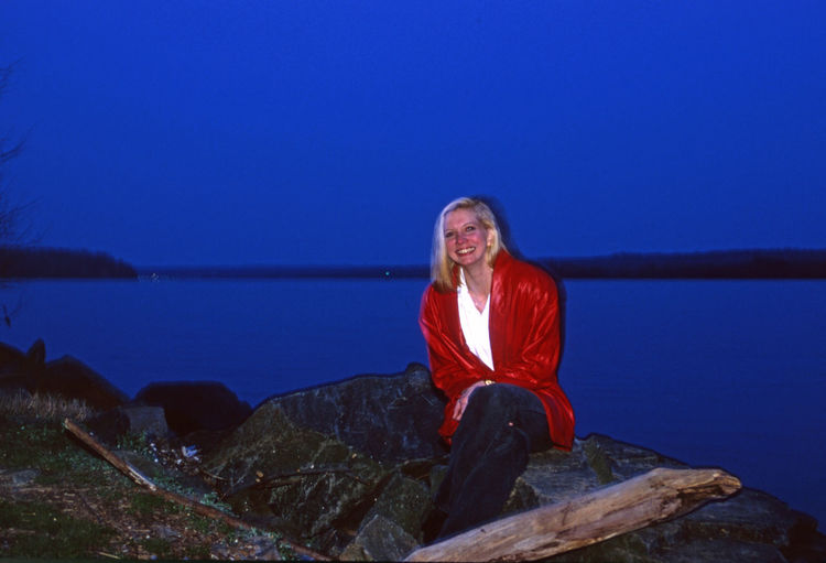 Portrait of smiling young woman sitting on rock against lake