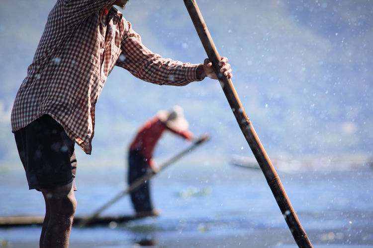 Midsection Of Man Holding Oar In Lake
