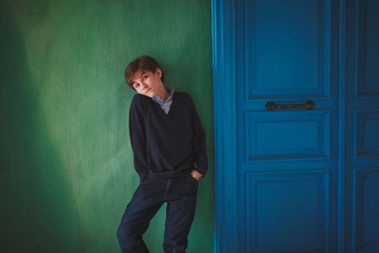 A serious cute teen boy with blue eyes is standing by the green wall. Next to a bright blue door. Pensive Blue Boy Casual Clothing Childhood Contemplation Door Front View Green Color Indoors  Lifestyles Looking Looking Away One Person Real People Standing Teenager Three Quarter Length Young Adult