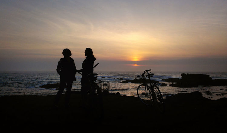 Silhouettes of two friends and their bikes, watching the sunset over the ocean Biking HUAWEI Photo Award: After Dark Beach Bike Friend Friendship Horizon Horizon Over Water Leisure Activity Lifestyles Positive Emotion Real People Sea Silhouette Sky Sunset Togetherness Two People Water