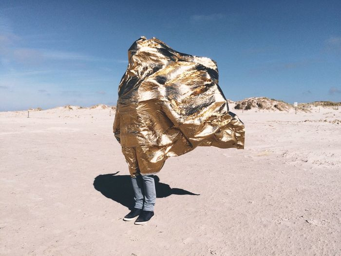 Person covered with golden sheet standing at sankt peter-ording beach against sky