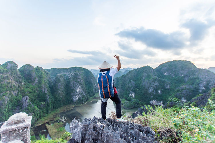 travel at Trang An, Ninh Binh, Vietnam Mountain One Person Human Arm Rock Sky Solid Rock - Object Leisure Activity Beauty In Nature Real People Lifestyles Scenics - Nature Arms Raised Cloud - Sky Full Length Nature Rear View Standing Holiday Vacations Mountain Range Limb Outdoors