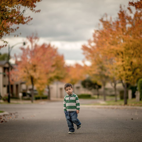 Boy standing on street amidst trees during autumn