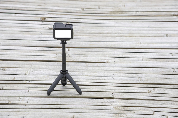 Camera and video with small black stand on a bamboo floor. SUPPORT Telephoto Screen Nobody Adjustable Plastic Vertical Stability Lens Camcorder Media Zoom Business Mobile Image Film Photographing New Shot Photographic Photographer Small Professional Digital Photograph Photography Object Photo Technology Tool Design Wood Metal Light Background Black Camera Compact Equipment Fast Flexible Hold Legs Mini Modern Portable Protection Tripod Tripods Video