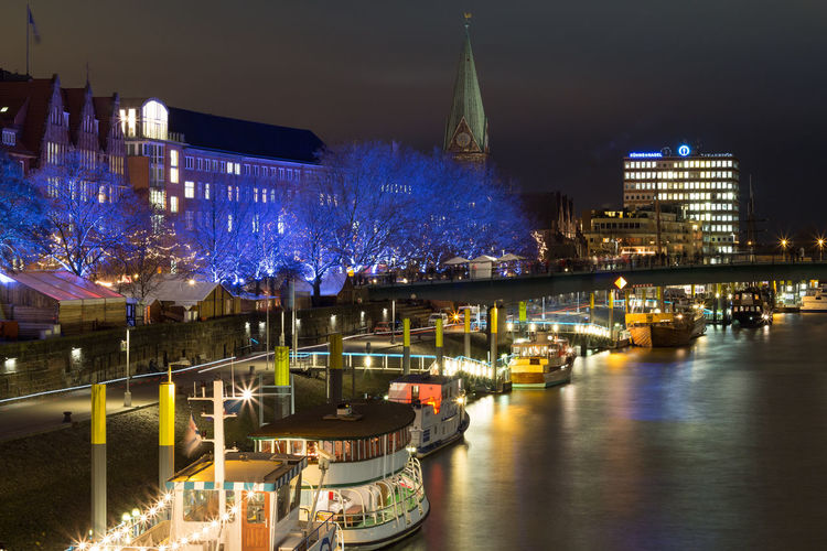 Boats moored on river by illuminated buildings at night