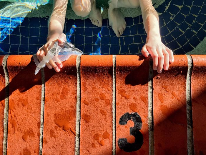 Close-Up Of Hands On Swimming Pool