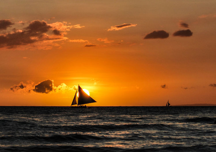 Silhouette sailboat in sea against orange sky