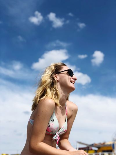 Cheerful young woman wearing sunglasses and bikini top against sky during summer