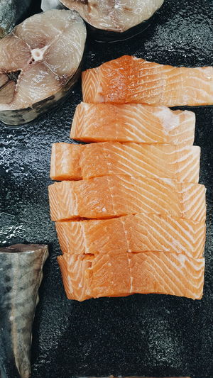Directly Above Shot Of Sliced Salmon Fish On Black Marble