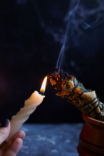 Close-up of hand holding burning candle and a sage stick for healing energies