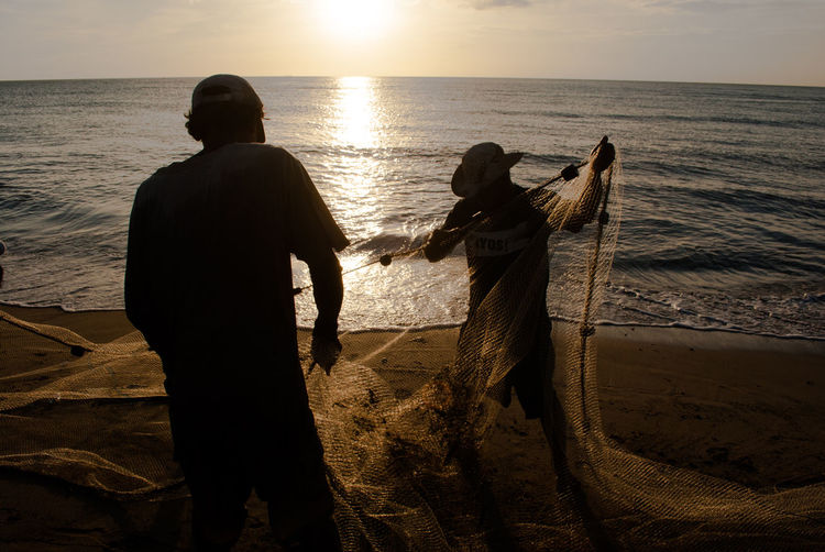 Two people with fishing nets on shore