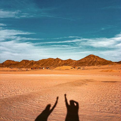 Shadow of people on desert land against sky
