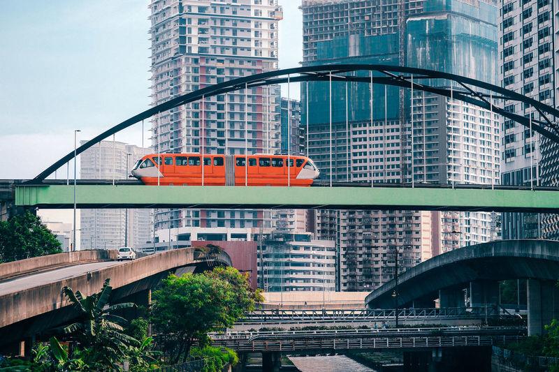 Train on railway bridge against buildings in city