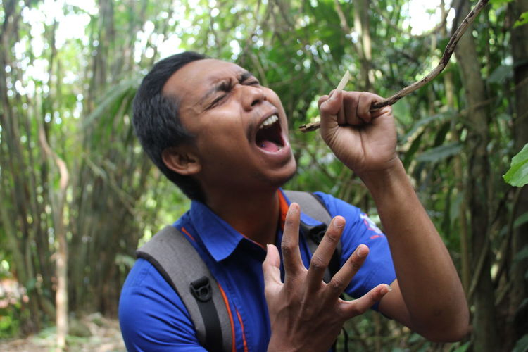 Young Man Screaming While Holding Twig In Forest