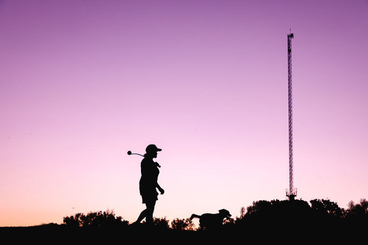 Silhouette woman and a dog standing against pink sky during sunset