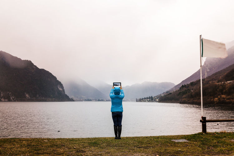 Rear view of woman photographing with digital tablet by lake during foggy weather