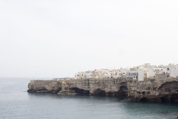Buildings on cliff by sea at polignano a mare against sky