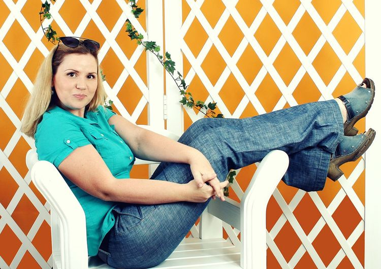Portrait of mid adult woman sitting with feet up on chair against white fence