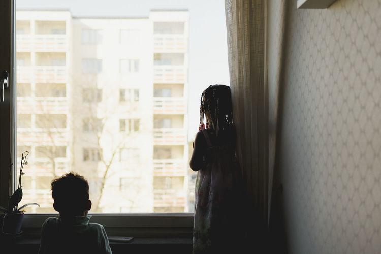 Rear view of people looking through window
