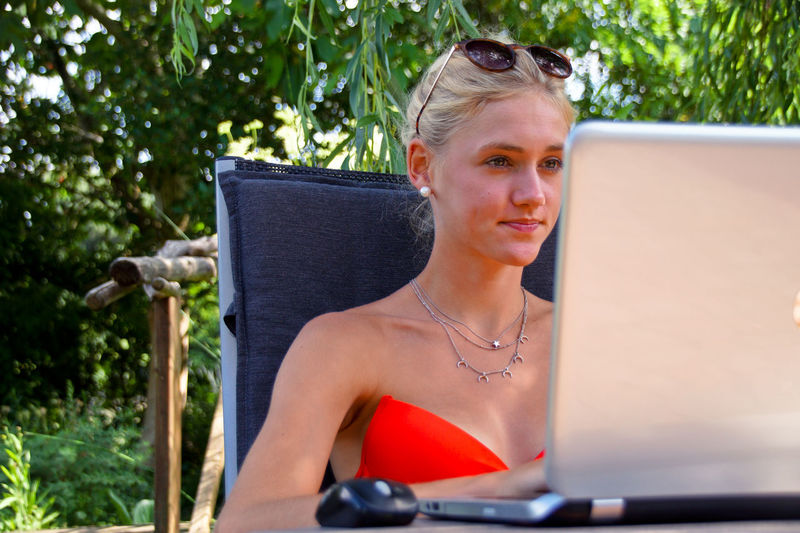 Young Woman Using Laptop While Sitting Against Plants In Yard
