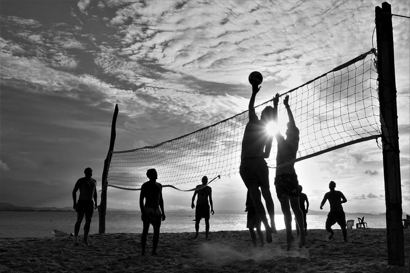 People playing with volleyball at beach