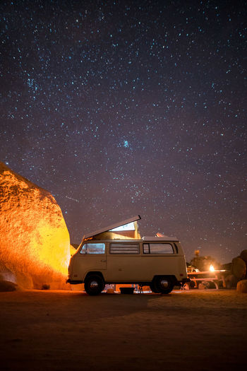 Van on field against star field in sky at night